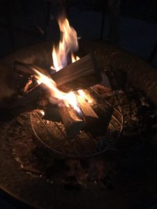 Small campfire in a firepit warms the evening with its glowing flames.