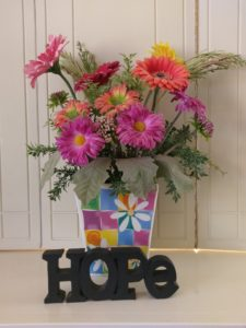 A bright, colorful arrangement of flowers, with the word HOPE at it's base.