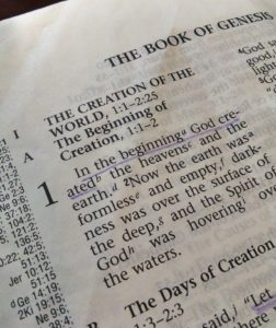 "The first page of Genesis from the Bible. ""In the beginning"" is underlined."