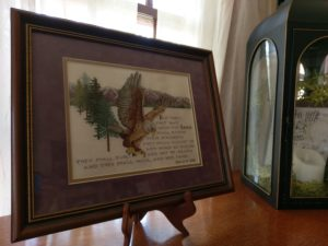 A framed cross stitched picture of an eagle in flight. The verse below it is Isaiah 40:31