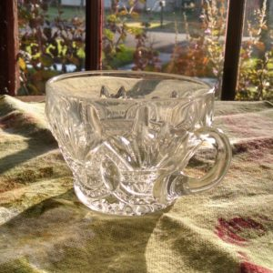 My Momma's clear, crystal punch cup. It sits in front of a window with the sun shining through the glass.