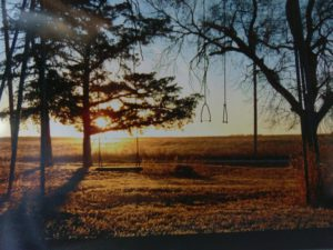 An old homemade swing set in the big backyard of a farm. The sun is setting in the background.