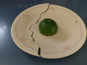 This picture is of a small white dessert plate with blue lines and clusters of small pink roses running around the edge. The plate sits on a blue counter, and has half of a lime upside down in its center.