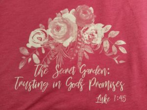 "Pink T-shirt with white roses. Imprinted on the front is: ""The Secret Garden: Trusting in God's Promises Luke 1:45"""
